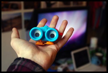 Pair of toy binoculars with eyes sitting in someone's open palm and looking back a them.