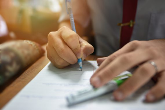 Student holding a pen taking lecture note or doing writing assignment in the classroom; closed up photo of young learner using a pen during the written test in collage or university training center - Image