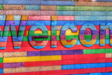 A colourful wall made of wood, with the word Welcome.