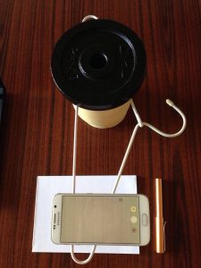 Smartphone suspended above a writing pad by a coathanger weighted down by an elevated weight