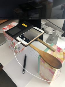 An iPhone held above a piece of paper by two wooden kitchen utensils propped on top of tissue boxes.