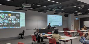 Photograph of a classroom where one projection screen displays the Zoom video feed, and the other displays the class slidedeck.