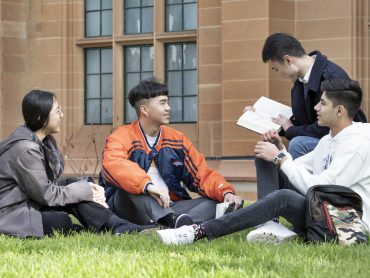 Group of international students sitting on the lawn outside Anderson Stuart Building