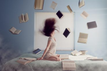 Image of woman throwing all her books in the air